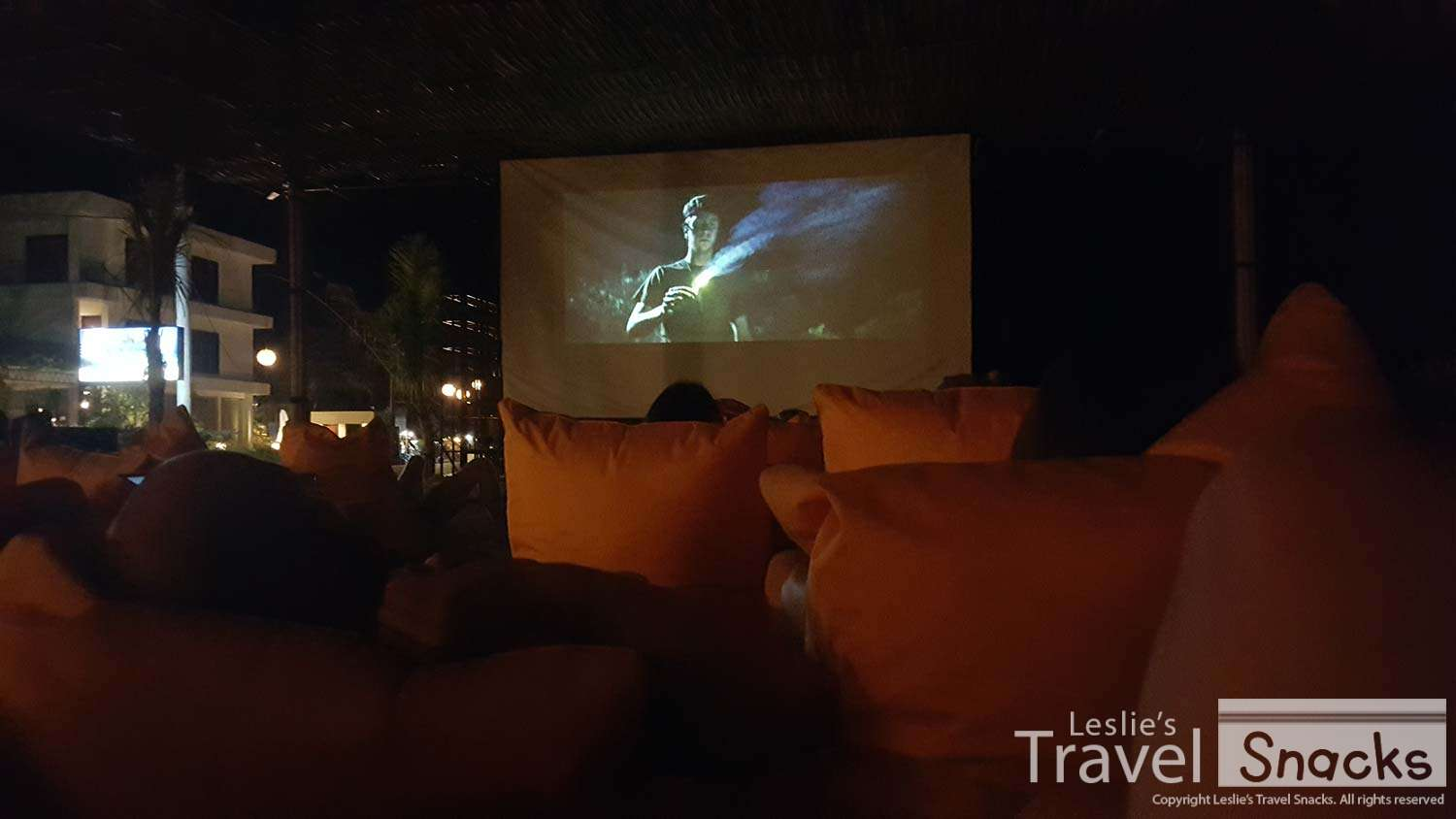 Watching King Kong in bean bag chairs on the sand.